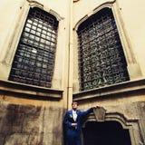 El novio se coloca en el ángulo debajo de ventanas viejas grandes Foto de archivo libre de regalías