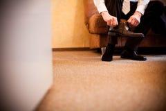 El novio se prepara para casarse y los lazos sus zapatos fotos de archivo libres de regalías