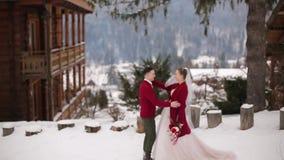El novio viene a la novia, abrazos y la besa en pueblo de montaña nevoso en la estación de esquí Pares románticos de la boda en h metrajes