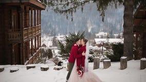 El novio viene a la novia, abrazos y la besa en pueblo de montaña nevoso en la estación de esquí Pares románticos de la boda en h