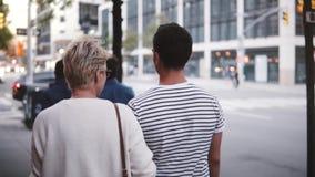 El novio y la novia de la cámara lenta que caminan juntos a lo largo de una calle hermosa de New York City que discute vida, incl almacen de video