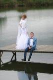El novio y la novia en el embarcadero de madera fotografía de archivo libre de regalías
