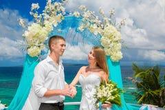 El novio y la novia felices con los anillos de bodas debajo del arco adornan Imagenes de archivo