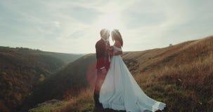 El novio y la novia hermosos se unen en el pico de la montaña almacen de metraje de vídeo