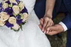 El novio y las manos del control de la novia Foto de archivo