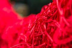 El nudo de la cuerda roja para los pares preciosos desea en templo con el foco selectivo Imagenes de archivo
