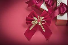 El nudo de la Navidad envolvió giftboxes en los días de fiesta rojos del fondo concentrados imagenes de archivo