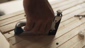 El nuevo arma moderno de la grapa se coloca en la tabla de madera en almacén y se toma a mano almacen de video