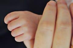 El nuevo bebé sostiene el pulgar de las madres Foto de archivo