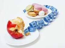 El nuevo concepto de la dieta, pregunta firma adentro la forma de la cinta de la medida entre la manzana roja y el buñuelo aislad imagen de archivo
