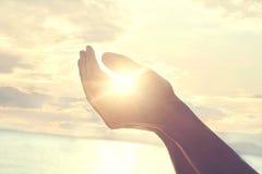 El nuevo día comienza con la salida del sol protegida en las manos de una mujer foto de archivo libre de regalías