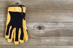 El nuevos cuero y nilón trabajan guantes en los tableros de madera rústicos fotos de archivo libres de regalías