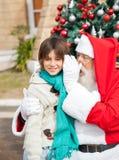El oído de Santa Claus Whispering In Boy Fotografía de archivo