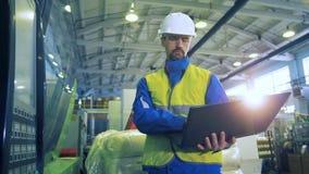 El obrero con un ordenador portátil está observando un indicador digital almacen de video