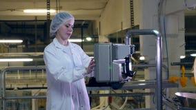 El obrero de la comida controla un transportador, usando una máquina almacen de video