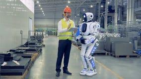 El obrero de sexo masculino está controlando remotamente el robot y están caminando juntos almacen de video