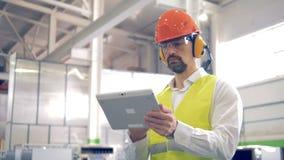 El obrero es permanente y de trabajo con su tableta en un almacén de la fábrica almacen de metraje de vídeo