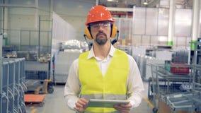 El obrero está caminando a través de fábrica y está tomando notas en su tableta almacen de video