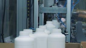 El obrero toma las botellas plásticas de un transportador, línea automatizada metrajes