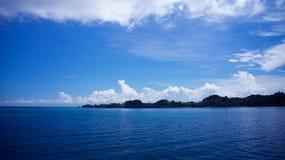 El océano con los cielos azules brillantes y las nubes blancas Imagen de archivo