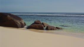 El océano lava piedras grandes en la orilla de Seychelles metrajes