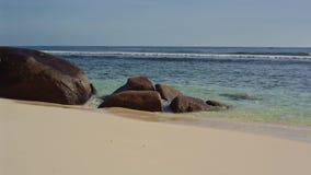 El océano lava piedras grandes en la orilla de Seychelles almacen de metraje de vídeo
