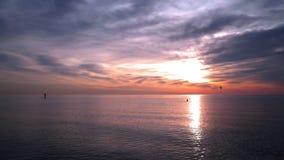 El océano Sunset Hombre en la tabla hawaiana en el océano de la puesta del sol Puesta del sol en el océano con agua tranquila almacen de video