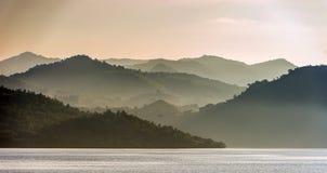 El océano y las montañas ajardinan en la mañana de niebla Fotografía de archivo