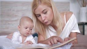 El ocio de la familia, mamá lee un libro a su hija del bebé que escuche ella con el interés que miente en cama almacen de video