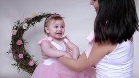El ocio feliz de la familia, madre joven pasa tiempo con el bebé en vestido rosado en sitio almacen de metraje de vídeo