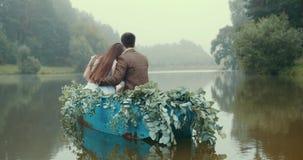 El ocuple cariñoso está disfrutando de la naturaleza del lago brumoso mientras que flota en el barco romántico adornado con las h almacen de metraje de vídeo
