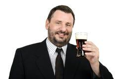El officeman sonriente sostiene el vidrio de cerveza inglesa Fotografía de archivo