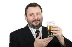 El oficial barbudo sostiene una cerveza dorada de cristal Fotografía de archivo libre de regalías