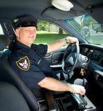 El oficial de policía conduce el coche patrulla Foto de archivo