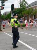 El oficial de policía de sexo femenino mira el cuarto del parad de julio Imagenes de archivo
