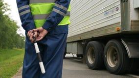 El oficial de policía del camino de la opinión de la parte trasera controla el camión que conduce más allá metrajes
