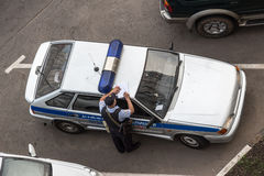 El oficial de policía hace una entrada que se inclina en el tejado del coche Fotografía de archivo