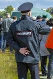 El oficial de policía de sexo masculino se ocupa orden público el día de fiesta, vista posterior fotografía de archivo