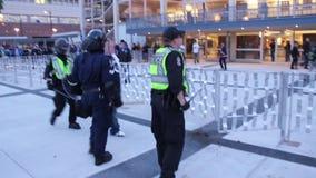 El oficial del alboroto balancea el bastón en el manifestante almacen de video