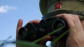 El oficial del ejército rojo mira a través de los prismáticos metrajes