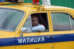 El oficial del servicio de la patrulla del camino que conduce el coche policía del ` de Volga del ` GAZ-24 Foto de archivo