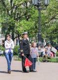 El oficial naval con una hija y una bandera Fotos de archivo