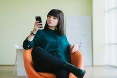 El oficinista de sexo femenino hermoso joven se sienta en una oficina minimalista en la parte posterior y utiliza el teléfono Tra Fotos de archivo libres de regalías