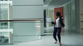 El oficinista despreocupado está bailando en el pasillo que sostiene el papel entonces que lanza la carpeta lejos y que relaja el almacen de metraje de vídeo