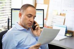 El oficinista habla en documentos de la lectura del smartphone imagen de archivo