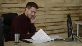 El oficinista joven habla en el teléfono y cheking sus documentos almacen de video