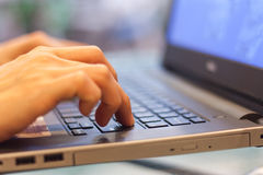 El oficinista mecanografía en el teclado del ordenador portátil imagen de archivo