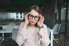El oficinista tiene un dolor de cabeza La muchacha aumentó sus manos a su cabeza con un dolor de cabeza imagenes de archivo