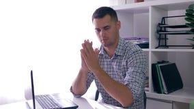 El oficinista trastornado mira la pantalla del ordenador portátil durante su trabajo que se sienta en la tabla dentro almacen de video