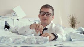 El oficinista va loco el oficinista en una camisa blanca y los vidrios que se ahogaban en una pila grande de papel y dejaron almacen de video